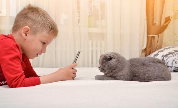 Dziecko leży na łóżku i fotografuje kota przez telefon