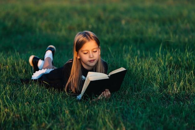 Dziecko leży na trawie i czyta książkę w świetle zachodzącego słońca.