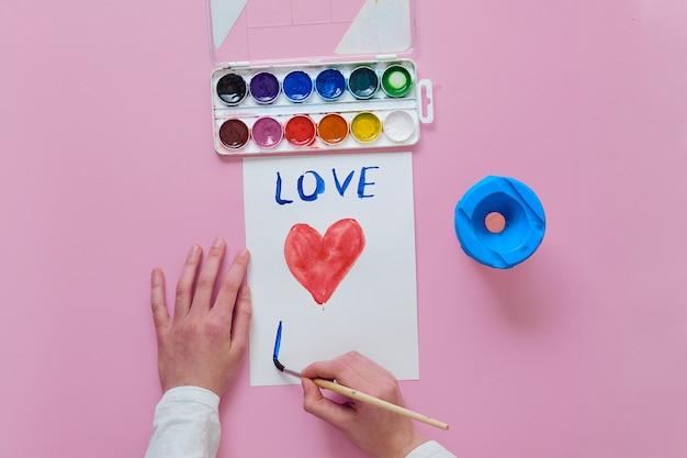 Dziecko losuje kartę na dzień matki, używa pędzla i farb akwarelowych