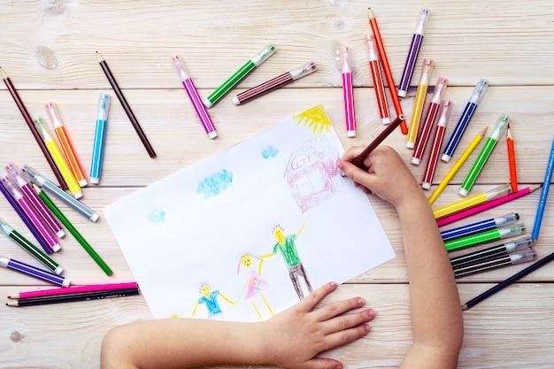Dziecko losuje kartę urodzinową ze swoją rodziną. rysunek wykonany przez dziecko z kolorowymi flamastrami i ołówkami