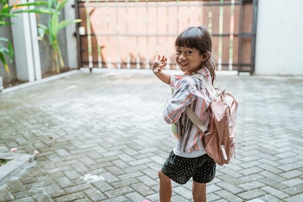 Dziecko macha na pożegnanie przed wyjściem do szkoły