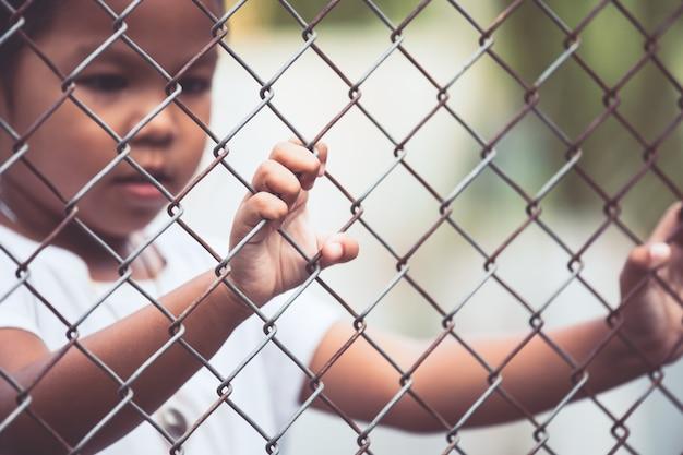 Dziecko mała dziewczynka ręka trzyma stalową siatkę w rocznika koloru brzmieniu