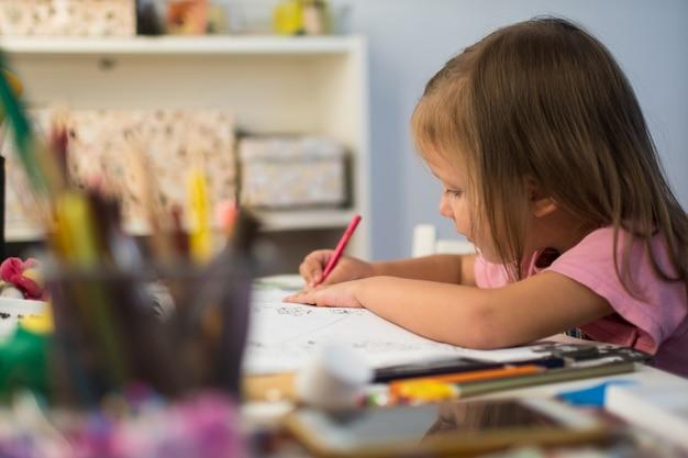 Dziecko mała dziewczynka rysuje ołówki w domu