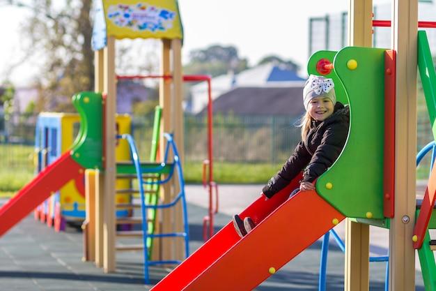 Dziecko mała ładna dziewczyna bawić się na boisku outdoors
