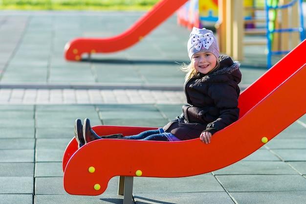 Dziecko mała ładna dziewczyna bawić się na boisku