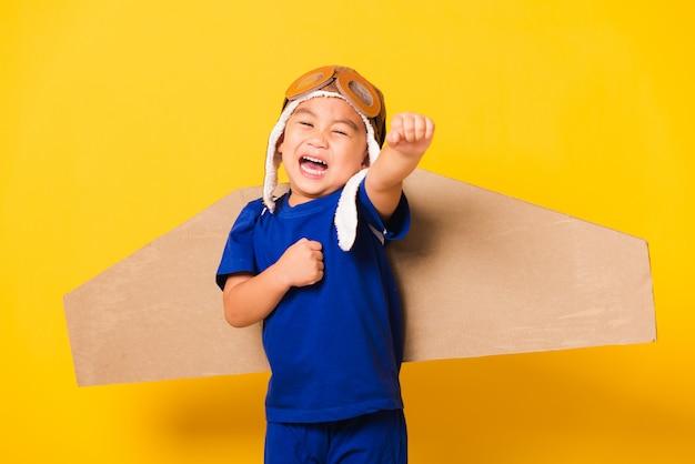 Dziecko małego chłopca z uśmiechem na sobie kapelusz pilota do zabawy i gogle z zabawkowymi kartonowymi skrzydłami samolotu