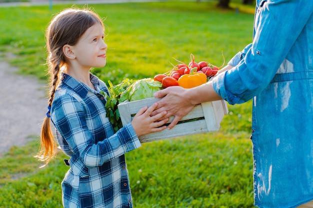 Dziecko małej dziewczynki mienia mama kosz świeżych organicznych warzyw z domowym ogródem.