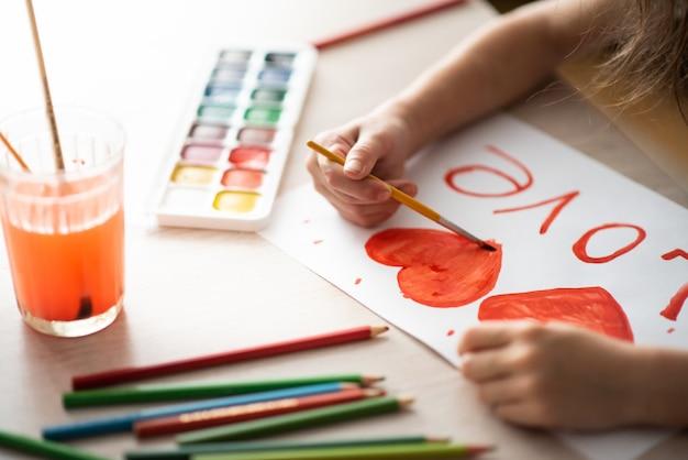 Dziecko maluje akwarelami akwarela czerwone serce na arkuszu krajobrazu na drewnianym stole