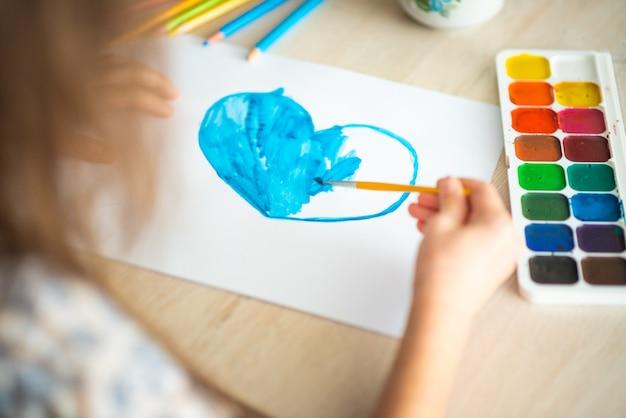 Dziecko maluje akwarelami akwarela klasyczne niebieskie serce na arkuszu krajobrazu na drewnianym stole