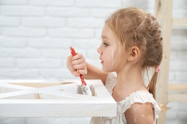 Dziecko maluje drewniane meble pędzlem i białym kolorem