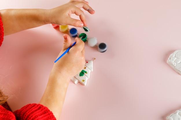 Dziecko maluje świąteczne zabawki. widok z góry