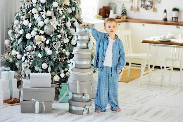 Dziecko - mały chłopiec w niebieskim piżamie stoi boso na tle choinki i trzyma w rękach wiele prezentów.