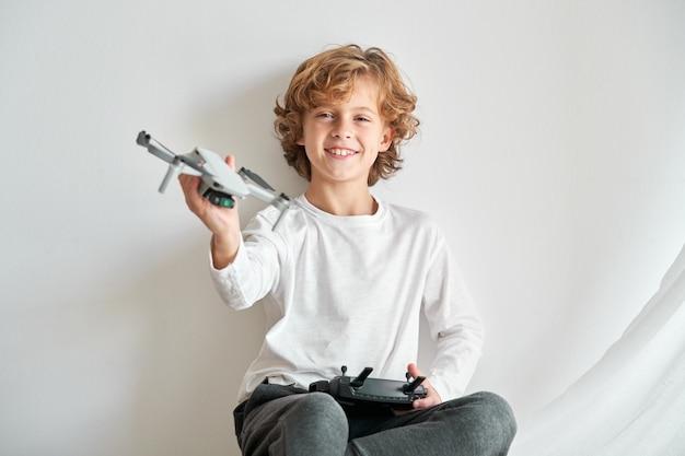 Dziecko manipulujące dronem i właśnie nadanym mu pilotem zdalnego sterowania