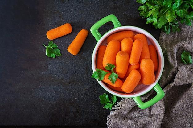 Dziecko marchewka wtyka w zielonym pucharze na czerni powierzchni. koncepcja zdrowego odżywiania. wegańskie jedzenie. widok z góry. leżał płasko