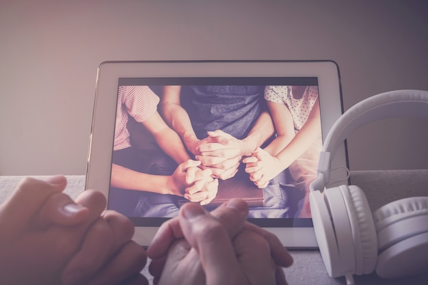 Dziecko modlące się z rodzicami za pomocą cyfrowego tabletu, rodzina i dzieci wspólnie modlą się online w domu