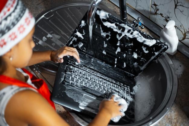 Dziecko myje laptopa w zlewie w kuchni