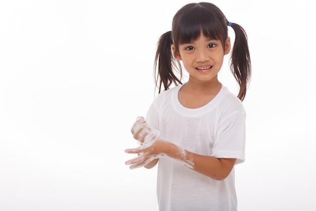 Dziecko myje ręce i pokazuje mydlane dłonie