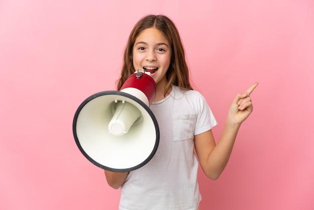 Dziecko na białym tle różowy krzycząc przez megafon i wskazując stronę