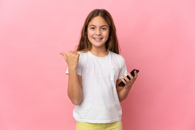 Dziecko na białym tle różowy przy użyciu telefonu komórkowego i wskazując na bok