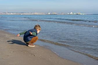 Dziecko na brzegu plaży gra z falami