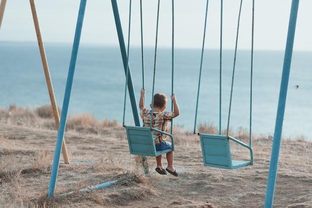 Dziecko na huśtawce kołyszące się blisko morza, w koszuli i dżinsowych szortach
