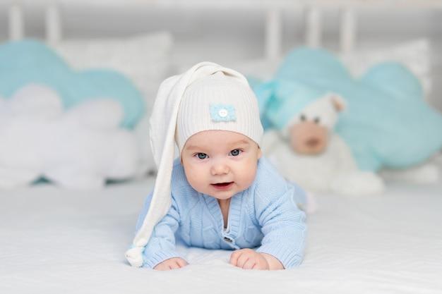 Dziecko na łóżeczku w kapturze kładzie się spać lub budzi się rano. tekstylia i pościel dla dzieci. noworodek z misiem zabawka
