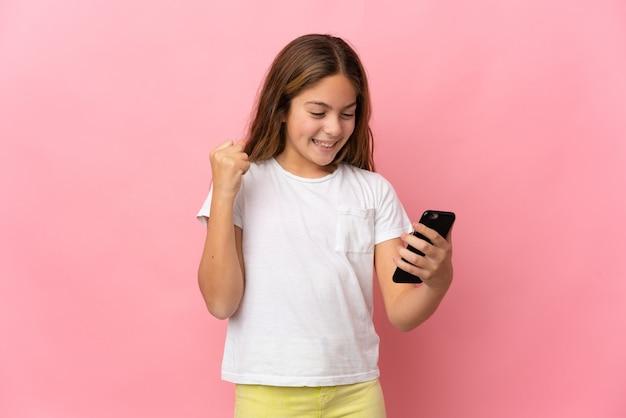Dziecko na na białym tle różowym tle za pomocą telefonu komórkowego i robi gest zwycięstwa
