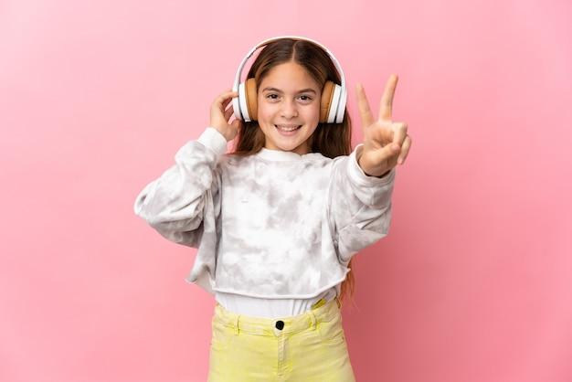 Dziecko na odosobnionym różowym tle słucha muzyki i śpiewu