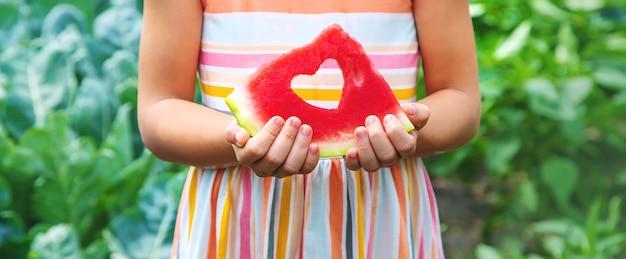 Dziecko na pikniku zjada arbuza.