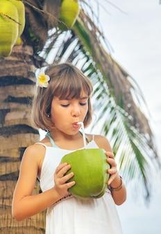 Dziecko na plaży pije kokos