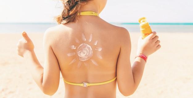 Dziecko na plaży rozmazuje krem przeciwsłoneczny. selektywna ostrość.