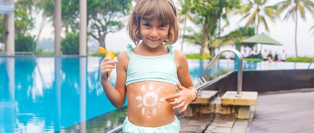 Dziecko na plaży z filtrem przeciwsłonecznym na plecach