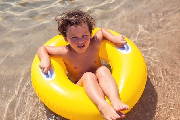 Dziecko na plaży z kółkiem do pływania. chłopiec pływa w morzu. koncepcja dzieci i wakacji