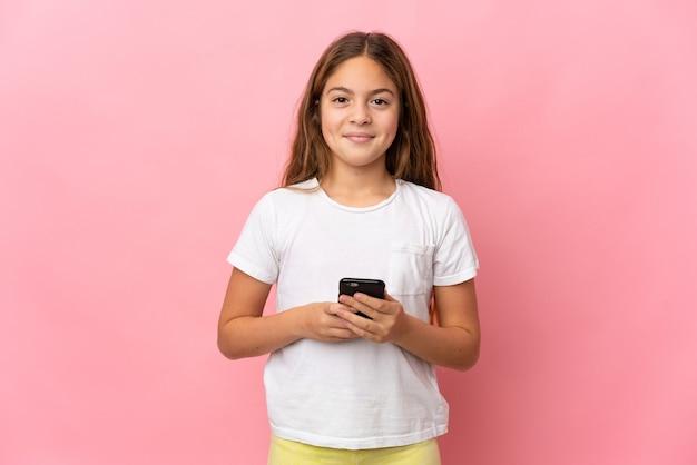 Dziecko na pojedyncze różowe patrząc w kamerę i uśmiechnięte podczas korzystania z telefonu komórkowego