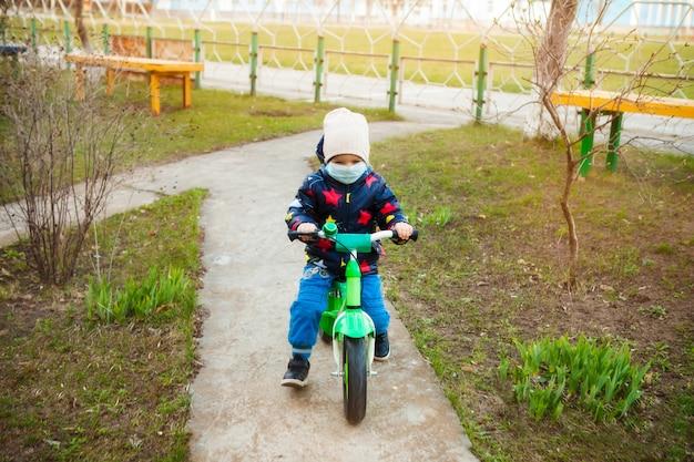 Dziecko na przejażdżce po parku miejskim w medycznej masce jeździ na rowerze. chodzenie po ulicy w okresie kwarantanny pandemii koronawirusa na świecie. środki ostrożności i nauczanie dzieci.
