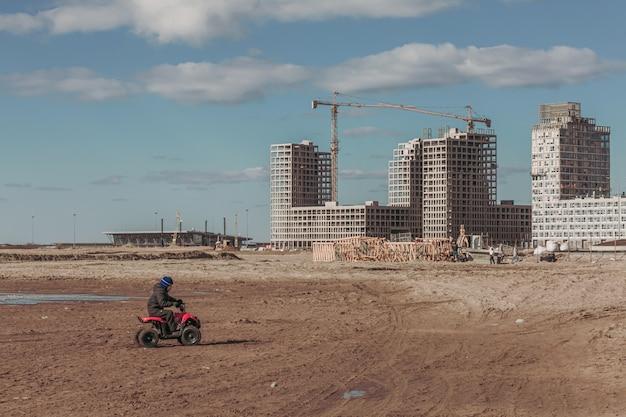 Dziecko na quadzie i panoramę z budową.