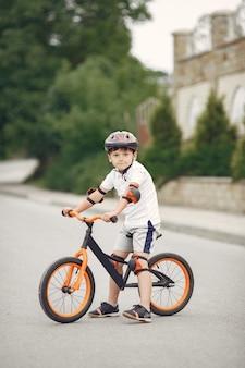 Dziecko na rowerze przy drodze asfaltowej latem. rower w parku