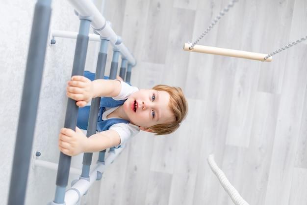 Dziecko na szwedzkiej ścianie uprawia sport w domu, chłopiec wspina się po drabinie z liną, pojęcie sportu i zdrowia