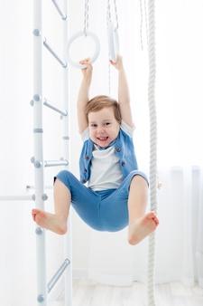 Dziecko na szwedzkiej ścianie uprawia sport w domu, chłopiec wspina się po drabinie z liną, pojęcie sportu i zdrowia.