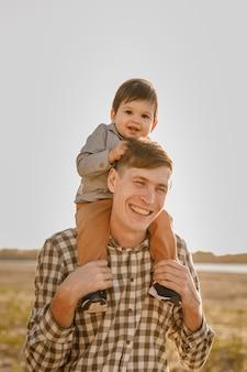 Dziecko na szyi ojca. spaceruj w pobliżu wody. dziecko i tata na tle nieba.