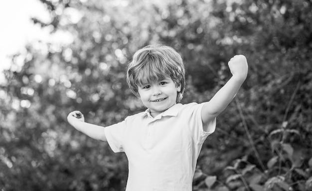 Dziecko na zewnątrz w przyrodzie. wesołe dziecko. zabawny chłopczyk na białym tle na tle zielonych drzew. uśmiechnięty chłopiec dziecko. wesoły wesoły dzieciak. szczęśliwy dzieciak chłopiec z rękami w górze
