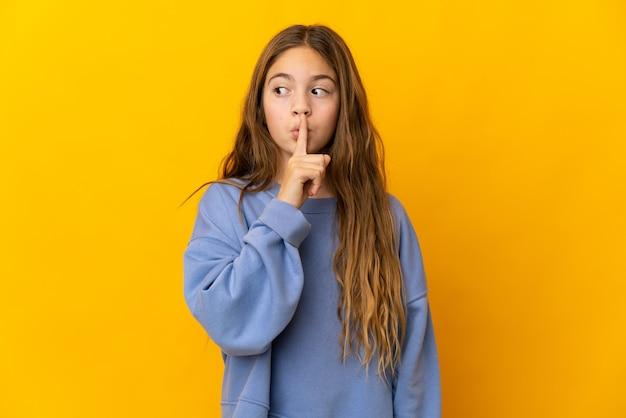 Dziecko nad izolowanym żółtą ścianą przedstawiającą znak gestu ciszy wkładając palec do ust