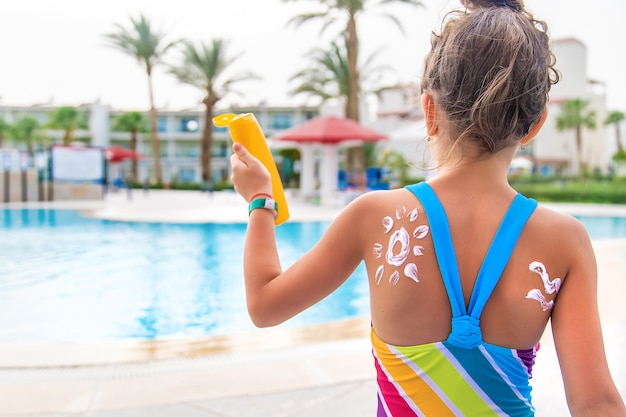 Dziecko nakłada krem przeciwsłoneczny na plecy.