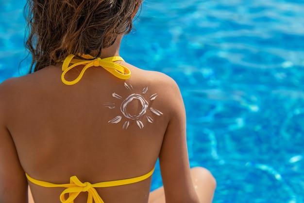 Dziecko nakłada na plecy krem z filtrem przeciwsłonecznym. selektywne skupienie. dziecko.