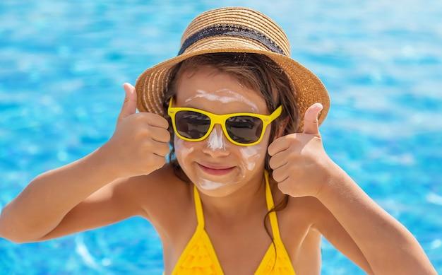 Dziecko nakłada na twarz krem przeciwsłoneczny. selektywne skupienie. dziecko.