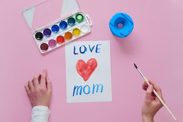 Dziecko narysowało kartę na dzień matki, używa pędzla i akwareli
