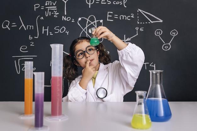 Dziecko naukowiec patrząc w kolbie z płynem chemicznym