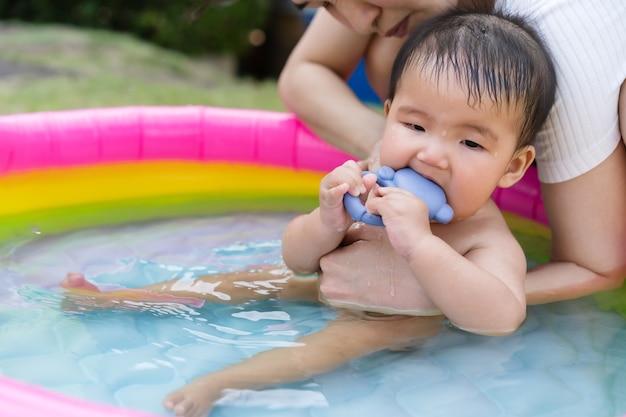 Dziecko niesione przez matkę bawiące się w nadmuchiwanym basenie