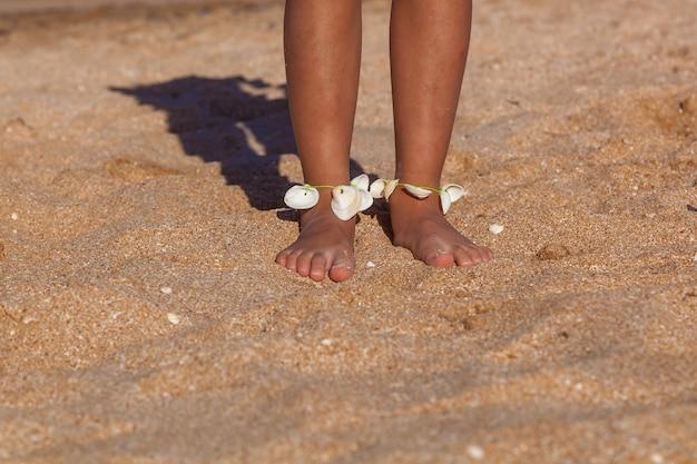 Dziecko nosi na nogach koraliki z muszelek. dziecko zrobiło koraliki z muszelek