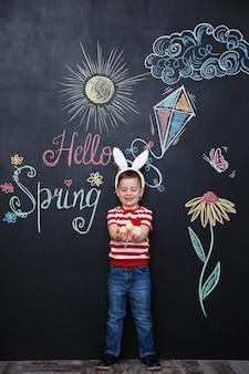 Dziecko nosi uszy królika i trzyma stos pisanek